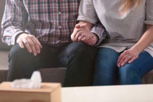 homem e mulher de mãos dadas com medo da morte