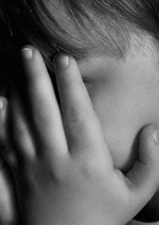Criança tampando o rosto com as mãos.