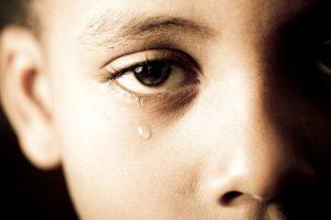 Imagem fechada no olho de uma criança triste, com lágrima escorrendo, representando o luto infantil.