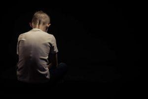 Criança vestindo blusa branca, sentada ao chão e de costas. Ao fundo, cor preta profunda. Conheça as fases do luto infantil!