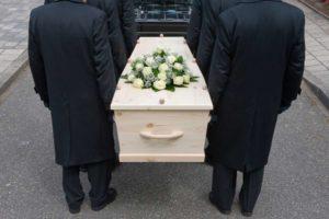 Seis pessoas com sobretudo preto carregando um caixão claro com flores em cima, três de cada lado. Momento antecede o sermão para funeral.