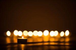 Na imagem, velas acesas desfocadas representando o sermão para funeral