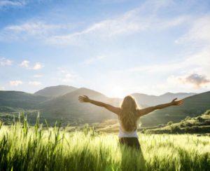 mulher de braços abertos em paisagem montanhosa, em meio a grama