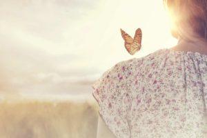 borboleta pousada no ombro de uma mulher