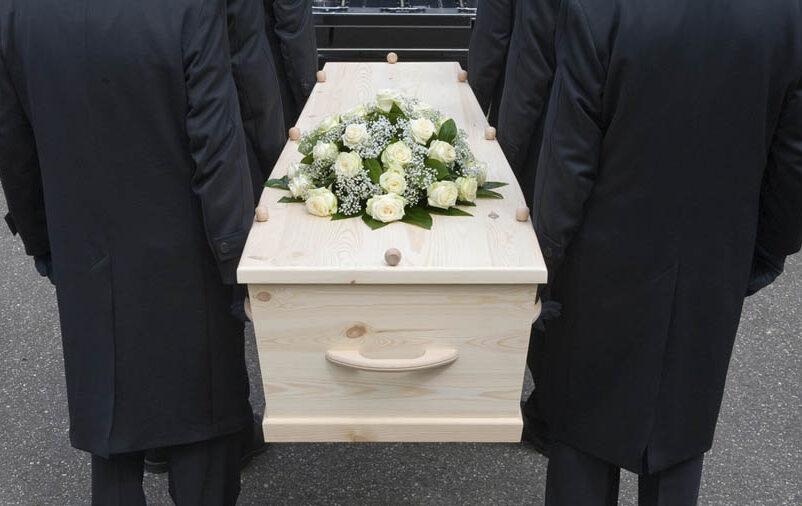 Pessoas segurando caixão saiba como funciona um plano funerário