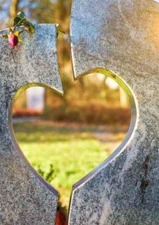 Cemitério jardim com uma pedra cortada em forma de coração em primeiro plano