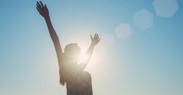 mulher de braços abertos celebrando a importância de ser grato
