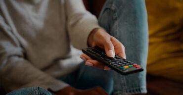 Pessoa segurando o controle assistindo as séries que abordam o luto