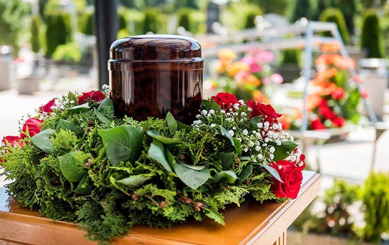 Vemos uma urna cinerária e coroa de flores. Veja se cremar faz mal ecologicamente!